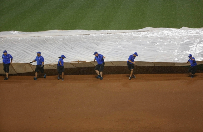 Aug 12, 2014; New York, NY, USA; The Citi Field grounds crew pulls the tarp as it rains during the third inning of the game between the New York Mets and the Washington Nationals. Mandatory Credit: Anthony Gruppuso-USA TODAY Sports