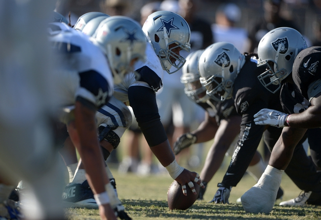 Aug 12, 2014; Oxnard, CA, USA; General view of the line of scrimmage as Dallas Cowboys center Mackenzy Bernadeau snaps the ball at scrimmage against the Oakland Raiders at River Ridge Fields. Mandatory Credit: Kirby Lee-USA TODAY Sports