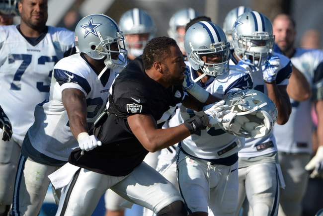 Aug 12, 2014; Oxnard, CA, USA; Oakland Raiders linebacker Justin Cole (46) is restrained by Dallas Cowboys players at scrimmage at River Ridge Fields. Mandatory Credit: Kirby Lee-USA TODAY Sports