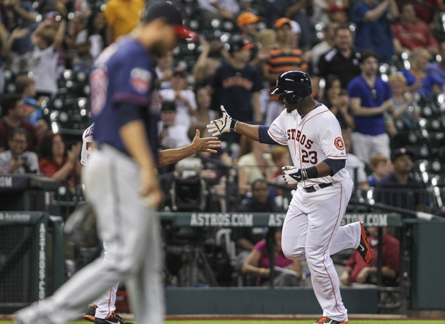 Aug 12, 2014; Houston, TX, USA; Houston Astros designated hitter Chris Carter (23) rounds the bases as Minnesota Twins starting pitcher Yohan Pino (63) reacts after Carter hits a home run during the fifth inning at Minute Maid Park. Mandatory Credit: Troy Taormina-USA TODAY Sports