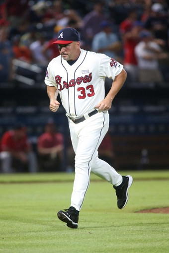 Aug 10, 2014; Atlanta, GA, USA; Atlanta Braves manager Fredi Gonzalez (33) jogs back to the dugout after a pitcher change during their game against the Washington Nationals at Turner Field. The Braves won 3-1. Mandatory Credit: Jason Getz-USA TODAY Sports