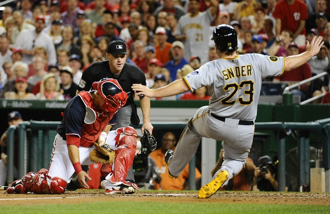 Aug 15, 2014; Washington, DC, USA; Pittsburgh Pirates right fielder Travis Snider (23) slides safely in to home to score a run as Washington Nationals catcher Wilson Ramos (40) is unable to control the ball during the game at Nationals Park. Mandatory Credit: Brad Mills-USA TODAY Sports