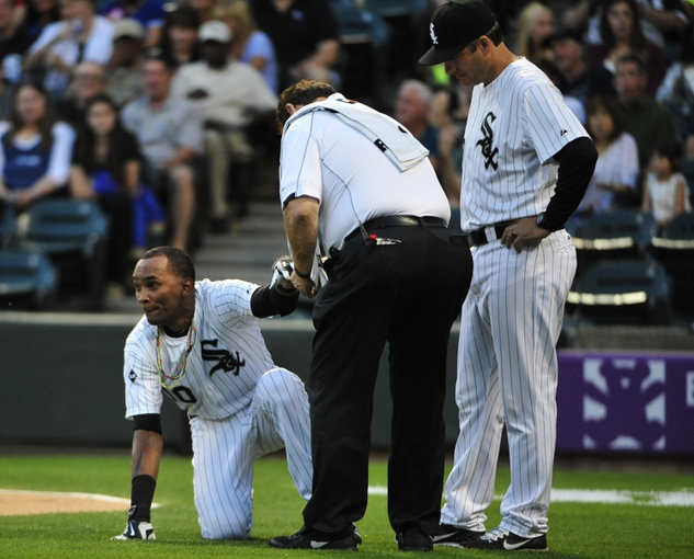 Aug 15, 2014; Chicago, IL, USA; Chicago White Sox shortstop Alexei Ramirez (10) is looked at by the trainer after getting hit by a pitch as  manager Robin Ventura (23) looks on against the Toronto Blue Jays during the first inning at U.S Cellular Field. Mandatory Credit: David Banks-USA TODAY Sports