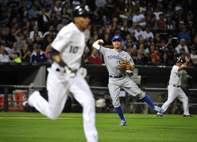 Aug 15, 2014; Chicago, IL, USA;  Chicago White Sox shortstop Alexei Ramirez (10) beats out an infield single as Toronto Blue Jays third baseman Danny Valencia (15) tries to throw him out during the fifth inning at U.S Cellular Field. Mandatory Credit: David Banks-USA TODAY Sports