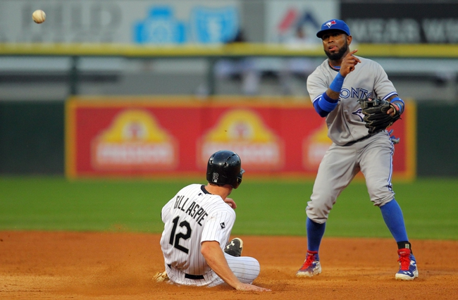 Aug 16, 2014; Chicago, IL, USA; Toronto Blue Jays shortstop Jose Reyes (right) throws to first to complete a double play after forcing out Chicago White Sox third baseman Conor Gillaspie (12) during the fifth inning at U.S Cellular Field. Mandatory Credit: Dennis Wierzbicki-USA TODAY Sports