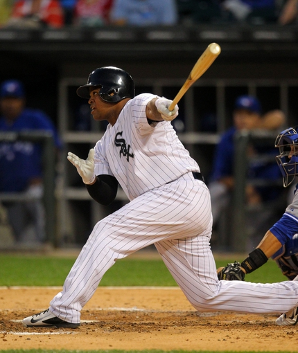 Aug 16, 2014; Chicago, IL, USA; Chicago White Sox right fielder Dayan Viciedo (24) hits an RBI sacrifice fly during the sixth inning against the Toronto Blue Jays at U.S Cellular Field. Mandatory Credit: Dennis Wierzbicki-USA TODAY Sports