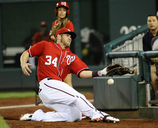 Aug 16, 2014; Washington, DC, USA; Washington Nationals right fielder Bryce Harper (34) is unable to make a sliding catch against the Pittsburgh Pirates during the ninth at Nationals Park. The Nationals won 4-3. Mandatory Credit: Brad Mills-USA TODAY Sports