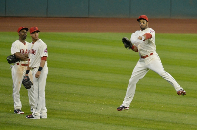 Aug 16, 2014; Cleveland, OH, USA; Cleveland Indians center fielder Michael Bourn (left) and left fielder Michael Brantley (center) watch as right fielder Chris Dickerson (38) leaps to grab a plastic bag during a pitching change in the ninth inning against the Baltimore Orioles at Progressive Field. Mandatory Credit: David Richard-USA TODAY Sports