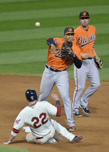 Aug 16, 2014; Cleveland, OH, USA; Baltimore Orioles shortstop J.J. Hardy (right) watches as second baseman Jonathan Schoop (6) turns a double play over Cleveland Indians second baseman Jason Kipnis (22) in the eighth inning at Progressive Field. Mandatory Credit: David Richard-USA TODAY Sports