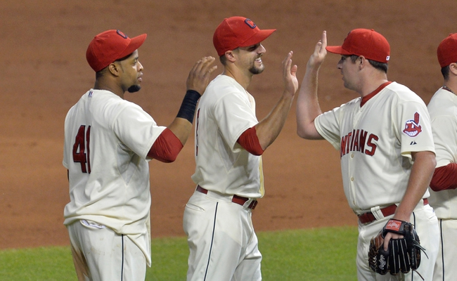 Aug 16, 2014; Cleveland, OH, USA; Cleveland Indians first baseman Carlos Santana (41), third baseman Lonnie Chisenhall (center) and relief pitcher Bryan Shaw (27) celebrate a 6-0 win over the Baltimore Orioles at Progressive Field. Mandatory Credit: David Richard-USA TODAY Sports