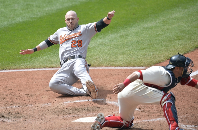 Aug 17, 2014; Cleveland, OH, USA; Baltimore Orioles first base Steve Pearce (28) scores beside Cleveland Indians catcher Yan Gomes (10) in the sixth inning at Progressive Field. Mandatory Credit: David Richard-USA TODAY Sports