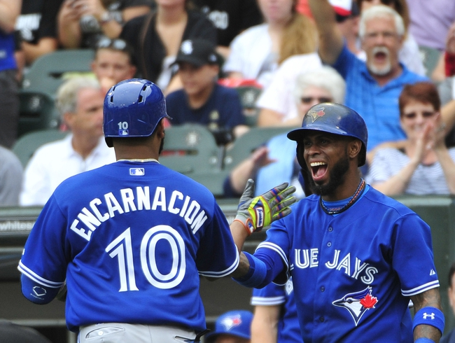 Aug 17, 2014; Chicago, IL, USA; Toronto Blue Jays designated hitter Edwin Encarnacion (10) is greeted by  shortstop Jose Reyes (7) after hitting two-run homer against the Chicago White Sox during the fifth inning at U.S Cellular Field. Mandatory Credit: David Banks-USA TODAY Sports