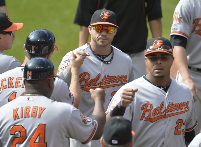 Aug 17, 2014; Cleveland, OH, USA; Baltimore Orioles first base Steve Pearce (center) and designated hitter Nelson Cruz (23) celebrate a 4-1 win over the Cleveland Indians at Progressive Field. Mandatory Credit: David Richard-USA TODAY Sports