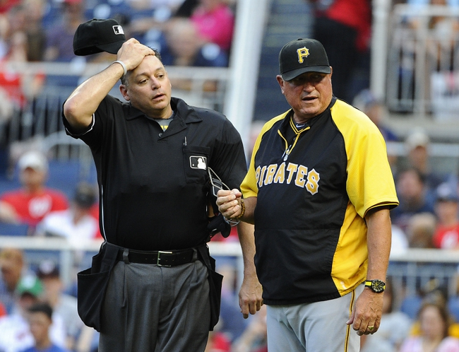 Aug 17, 2014; Washington, DC, USA; Pittsburgh Pirates manager Clint Hurdle (13) discusses a call with umpire Andy Fletcher (49) during the sixth inning against the Washington Nationals at Nationals Park. Mandatory Credit: Brad Mills-USA TODAY Sports