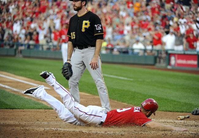 Aug 17, 2014; Washington, DC, USA; Washington Nationals left fielder Kevin Frandsen (19) scores a run as Pittsburgh Pirates first baseman Ike Davis (15) looks on during the seventh inning at Nationals Park. Mandatory Credit: Brad Mills-USA TODAY Sports