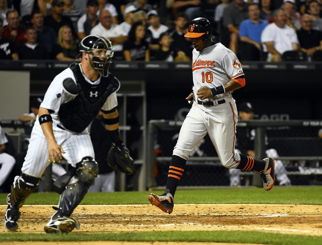 Aug 19, 2014; Chicago, IL, USA; Baltimore Orioles center fielder Adam Jones (10) scores a run against Chicago White Sox catcher Tyler Flowers (21) during the sixth inning at U.S Cellular Field. Mandatory Credit: Mike DiNovo-USA TODAY Sports