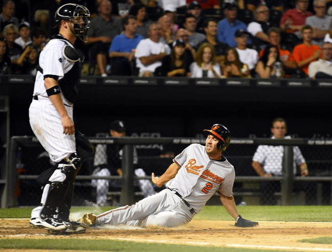 Aug 19, 2014; Chicago, IL, USA; Baltimore Orioles shortstop J.J. Hardy (2) slides to home plate against Chicago White Sox catcher Tyler Flowers (21) during the sixth inning at U.S Cellular Field. Mandatory Credit: Mike DiNovo-USA TODAY Sports