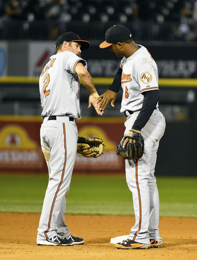 Aug 19, 2014; Chicago, IL, USA; Baltimore Orioles shortstop J.J. Hardy (2) reacts with second baseman Jonathan Schoop (6) after the ninth inning at U.S Cellular Field. Baltimore Orioles defeat the Chicago White Sox 5-1. Mandatory Credit: Mike DiNovo-USA TODAY Sports