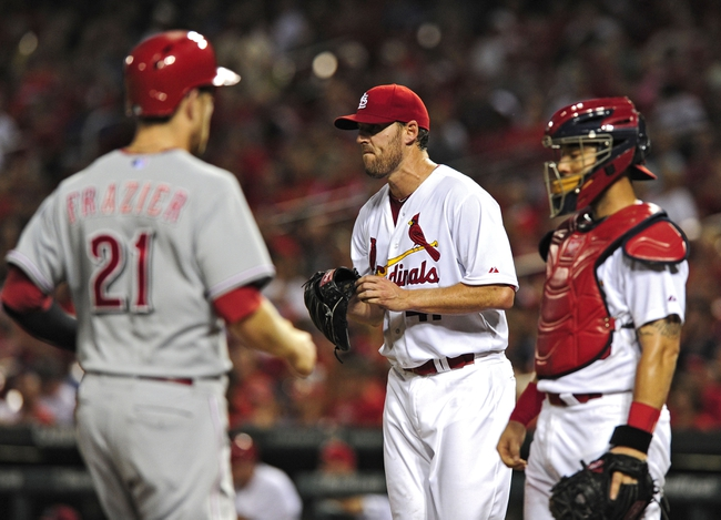 Aug 19, 2014; St. Louis, MO, USA; St. Louis Cardinals starting pitcher John Lackey (41) looks on as Cincinnati Reds third baseman Todd Frazier (21) scores on a two run double by left fielder Ryan Ludwick (not pictured) during the sixth inning at Busch Stadium. Mandatory Credit: Jeff Curry-USA TODAY Sports