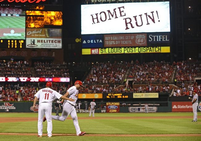Aug 19, 2014; St. Louis, MO, USA; St. Louis Cardinals shortstop Jhonny Peralta (27) is congratulated by third base coach Jose Oquendo (11) after hitting a solo home run off of Cincinnati Reds starting pitcher Alfredo Simon (31) during the sixth inning at Busch Stadium. Mandatory Credit: Jeff Curry-USA TODAY Sports