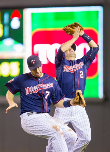 Aug 19, 2014; Minneapolis, MN, USA; Minnesota Twins first baseman Joe Mauer (7) and second baseman Brian Dozier (2) collide going for a fly ball in the sixth inning against the Cleveland Indians at Target Field. The Cleveland Indians win 7-5. Mandatory Credit: Brad Rempel-USA TODAY Sports