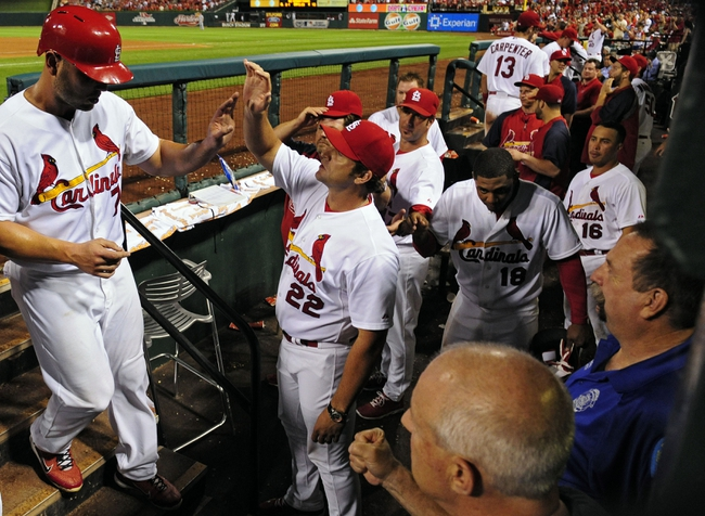 Aug 19, 2014; St. Louis, MO, USA; St. Louis Cardinals left fielder Matt Holliday (7) is congratulated by manager Mike Matheny (22) after being replaced by pinch runner Peter Bourjos (not pictured) during the ninth inning against the Cincinnati Reds at Busch Stadium. The Cardinals defeated the Reds 5-4. Mandatory Credit: Jeff Curry-USA TODAY Sports