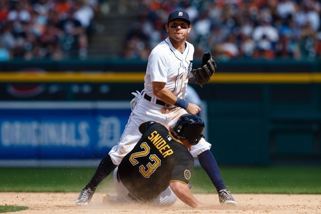 Aug 14, 2014; Detroit, MI, USA; Detroit Tigers second baseman Ian Kinsler (3) makes a throw to first as Pittsburgh Pirates left fielder Travis Snider (23) slides into second base at Comerica Park. Mandatory Credit: Rick Osentoski-USA TODAY Sports
