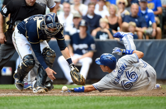 Aug 20, 2014; Milwaukee, WI, USA;  Toronto Blue Jays second baseman Munenori Kawasaki (66) scores on a base hit by shortstop Jose Reyes (not pictured) as the ball gets away from Milwaukee Brewers catcher Jonathan Lucroy (20) in the fifth inning at Miller Park. Mandatory Credit: Benny Sieu-USA TODAY Sports