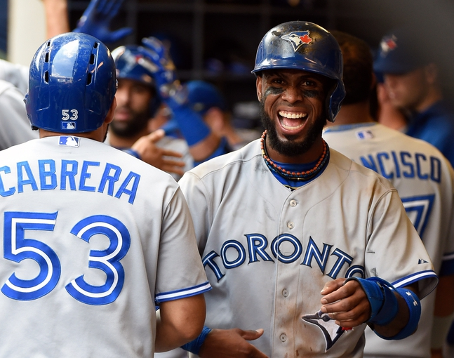 Aug 20, 2014; Milwaukee, WI, USA;  Toronto Blue Jays shortstop Jose Reyes (7) smiles in the dugout after scoring in the sixth inning during the game against the Milwaukee Brewers at Miller Park. Mandatory Credit: Benny Sieu-USA TODAY Sports