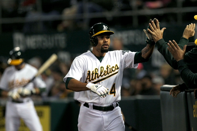 Aug 8, 2014; Oakland, CA, USA; Oakland Athletics DH Coco Crisp (4) is greeted at the dugout after scoring from third base on a wild pitch in the fifth inning of their MLB baseball game with the Minnesota Twins at O.co Coliseum. Mandatory Credit: Lance Iversen-USA TODAY Sports