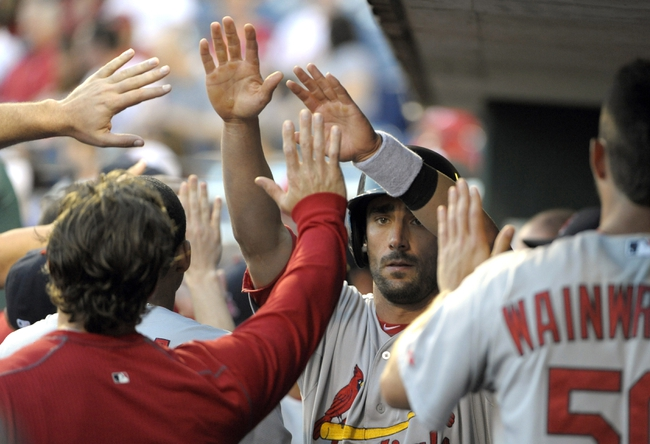 Aug 22, 2014; Philadelphia, PA, USA; St. Louis Cardinals third baseman Matt Carpenter (13) gets congratulations in the dugout after scoring a run during the first inning against the Philadelphia Phillies at Citizens Bank Park. Mandatory Credit: Eric Hartline-USA TODAY Sports