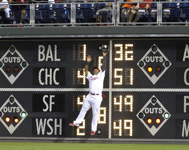 Aug 22, 2014; Philadelphia, PA, USA; Philadelphia Phillies right fielder Marlon Byrd (3) makes a catch against the wall in the eighth inning against the St. Louis Cardinals at Citizens Bank Park. The Phillies defeated the Cardinals, 5-4. Mandatory Credit: Eric Hartline-USA TODAY Sports