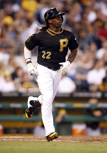 Aug 29, 2014; Pittsburgh, PA, USA; Pittsburgh Pirates center fielder Andrew McCutchen (22) runs to first base after hitting a single against the Cincinnati Reds during the fourth inning at PNC Park. Mandatory Credit: Charles LeClaire-USA TODAY Sports