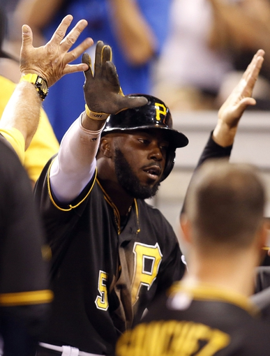Aug 29, 2014; Pittsburgh, PA, USA; Pittsburgh Pirates third baseman Josh Harrison (5) receives high-fives in the dugout after scoring a run against the Cincinnati Reds during the eighth inning at PNC Park. The Pirates won 2-1. Mandatory Credit: Charles LeClaire-USA TODAY Sports