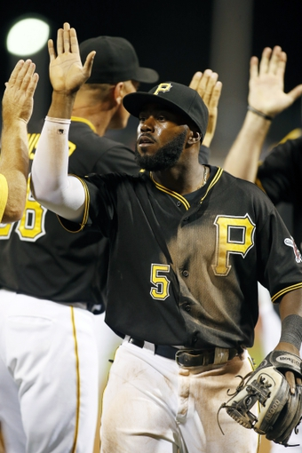 Aug 29, 2014; Pittsburgh, PA, USA; Pittsburgh Pirates third baseman Josh Harrison (5) celebrates with teammates after defeating the Cincinnati Reds at PNC Park. The Pirates won 2-1. Mandatory Credit: Charles LeClaire-USA TODAY Sports