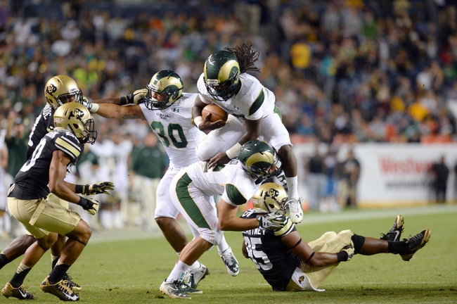 zzzAug 29, 2014; Denver, CO, USA; Colorado State Rams running back Dee Hart (10) leaps over tight end Nolan Peralta (32) and Colorado Buffaloes defensive end Derek McCartney (95) in the second quarter at Sports Authority Field at Mile High. Mandatory Credit: Ron Chenoy-USA TODAY Sports