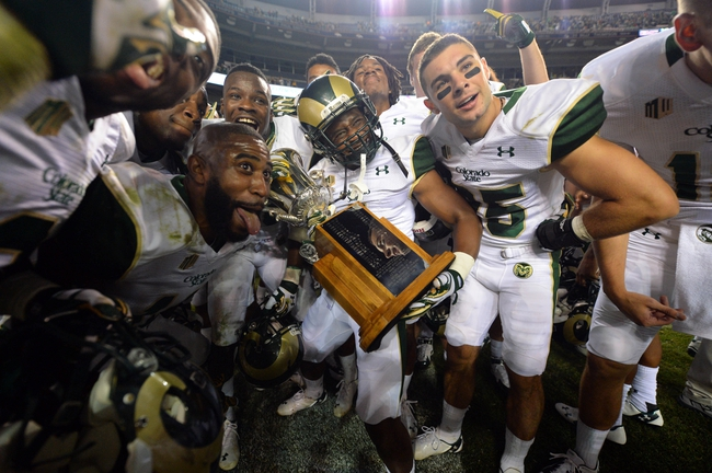Aug 29, 2014; Denver, CO, USA; Members of the Colorado State Rams react with the Centennial Cup following the win over the Colorado Buffaloes at Sports Authority Field at Mile High. Mandatory Credit: Ron Chenoy-USA TODAY Sports