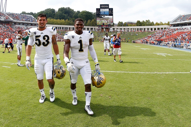 Aug 30, 2014; Charlottesville, VA, USA; UCLA Bruins linebacker Ryan Hofmeister (53) and Bruins defensive back Ishmael Adams (1) leave the field after their game against the Virginia Cavaliers at Scott Stadium. The Bruins won 28-20. Mandatory Credit: Geoff Burke-USA TODAY Sports