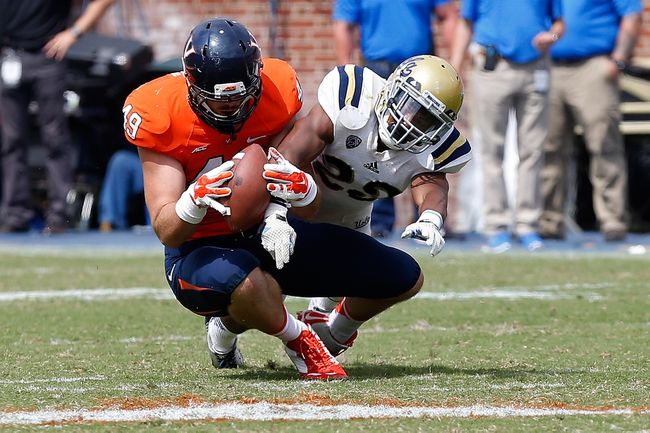 Aug 30, 2014; Charlottesville, VA, USA; Virginia Cavaliers tight end Zachary Swanson (49) catches the ball as UCLA Bruins defensive back Anthony Jefferson (23) defends in the third quarter at Scott Stadium. The Bruins won 28-20. Mandatory Credit: Geoff Burke-USA TODAY Sports