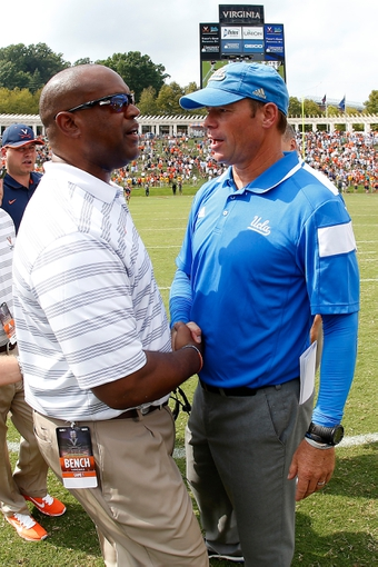 Aug 30, 2014; Charlottesville, VA, USA; Virginia Cavaliers head coach Mike London (left) shakes hands with UCLA Bruins head coach Jim Mora (right) after their game at Scott Stadium. The Bruins won 28-20. Mandatory Credit: Geoff Burke-USA TODAY Sports