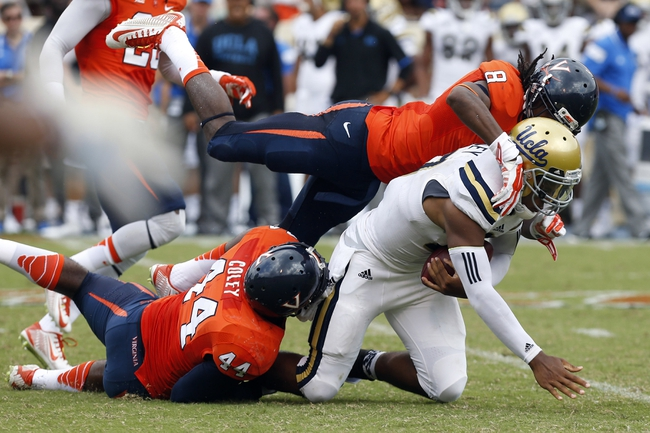 Aug 30, 2014; Charlottesville, VA, USA; UCLA Bruins quarterback Brett Hundley (17) runs with the ball as Virginia Cavaliers safety Anthony Harris (8) and Cavaliers linebacker Henry Coley (44) make the tackle the tackle in the third quarter at Scott Stadium. The Bruins won 28-20. Mandatory Credit: Geoff Burke-USA TODAY Sports
