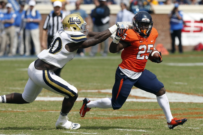 Aug 30, 2014; Charlottesville, VA, USA; Virginia Cavaliers running back Kevin Parks (25) carries the ball as UCLA Bruins linebacker Myles Jack (30) attempts the tackle in the fourth quarter at Scott Stadium. The Bruins won 28-20. Mandatory Credit: Geoff Burke-USA TODAY Sports