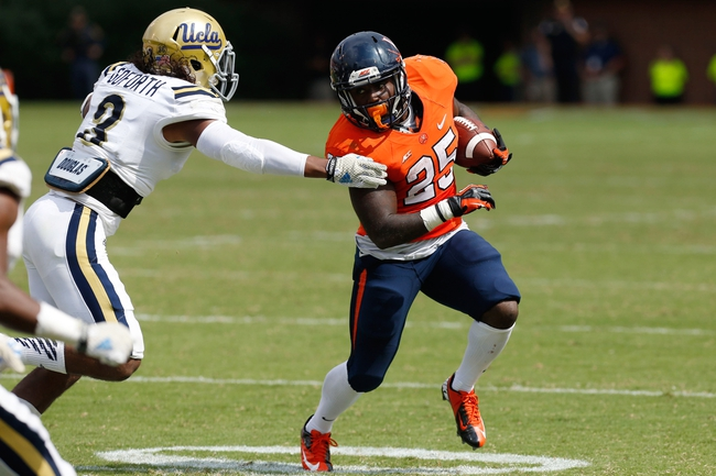 Aug 30, 2014; Charlottesville, VA, USA; Virginia Cavaliers running back Kevin Parks (25) carries the ball as UCLA Bruins defensive back Randall Goforth (3) attempts the tackle in the fourth quarter at Scott Stadium. The Bruins won 28-20. Mandatory Credit: Geoff Burke-USA TODAY Sports