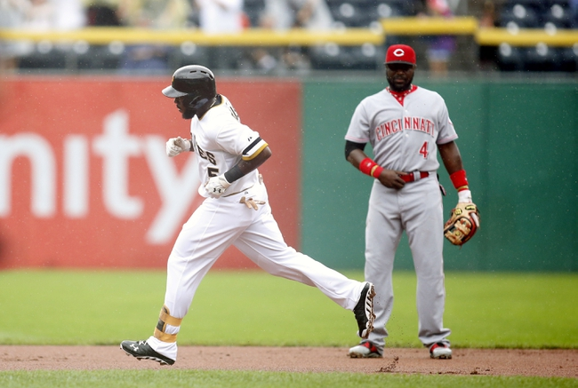 Aug 31, 2014; Pittsburgh, PA, USA; Pittsburgh Pirates third baseman Josh Harrison (5) rounds the bases after hitting a solo home run as Cincinnati Reds second baseman Brandon Phillips (4) looks on during the first inning at PNC Park. Mandatory Credit: Charles LeClaire-USA TODAY Sports