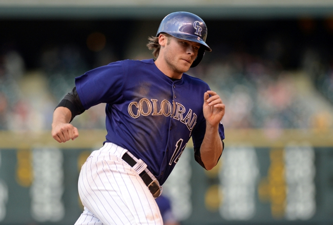 Sep 1, 2014; Denver, CO, USA; Colorado Rockies shortstop Josh Rutledge (14) heads home to score in the sixth inning against the San Francisco Giants at Coors Field. Mandatory Credit: Ron Chenoy-USA TODAY Sports