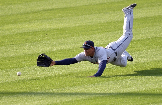 Sep 1, 2014; Cleveland, OH, USA; Detroit Tigers center fielder Ezequiel Carrera (61) dives for a base hit by Cleveland Indians left fielder Zach Walters (not pictured) in the sixth inning at Progressive Field. Mandatory Credit: David Richard-USA TODAY Sports