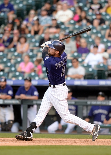 Sep 1, 2014; Denver, CO, USA; Colorado Rockies pinch hitter Ben Paulsen (4) hits a two run home run in the seventh inning against the San Francisco Giants at Coors Field. Mandatory Credit: Ron Chenoy-USA TODAY Sports