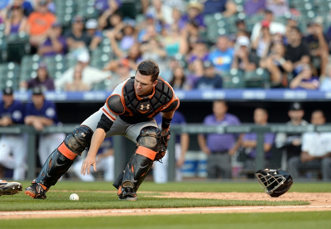 Sep 1, 2014; Denver, CO, USA; San Francisco Giants catcher Buster Posey (28) fields a bunt in in the seventh inning against the Colorado Rockies at Coors Field. Mandatory Credit: Ron Chenoy-USA TODAY Sports