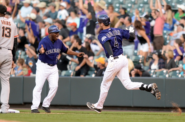Sep 1, 2014; Denver, CO, USA; Colorado Rockies pinch hitter Ben Paulsen (4) and first base coach Eric Young (21) celebrate his two run home run in the eighth inning against the San Francisco Giants at Coors Field. Mandatory Credit: Ron Chenoy-USA TODAY Sports