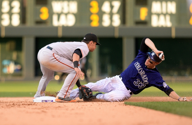 Sep 1, 2014; Denver, CO, USA; Colorado Rockies first baseman Justin Morneau (33) is caught stealing by San Francisco Giants second baseman Joe Panik (12) in the eighth inning at Coors Field. Mandatory Credit: Ron Chenoy-USA TODAY Sports